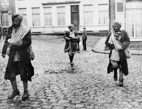 Image © IWM (Q 53348) - A group of wounded Indian soldiers walk across the cobbles of a French village.
