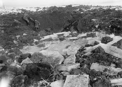 Image © IWM (Q 1684) – Officers inspecting chunks of ice broken up by shell fire on the battlefield at Beaumont Hamel, December 1916.