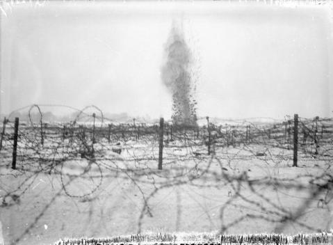 Image © IWM (Q 1688) – A shell bursting amongst the barbed wire entanglements on the battlefield at Beaumont Hamel, December 1916.
