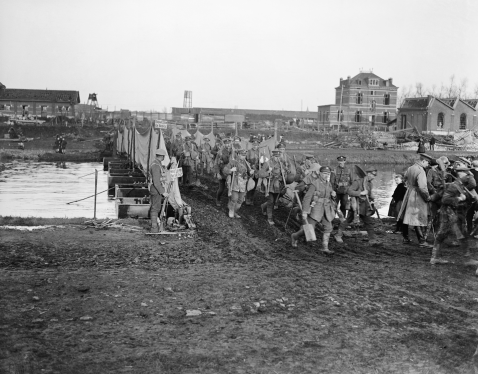 Image © IWM (Q 9650) – Troops of the 1/4th Battalion, South Lancashire Regiment (Pioneer Battalion of the 55th Division) crossing a pontoon bridge over the Scheldt river at Tournai, 9 November 1918.
