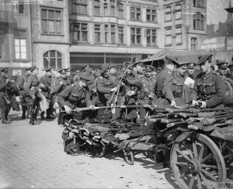 Image © IWM (Q 7545) – Demobilized men handing in their rifles before boarding the Rhine steamer. The steamer took them to Rotterdam on their way to England. Cologne, 23 April 1919.