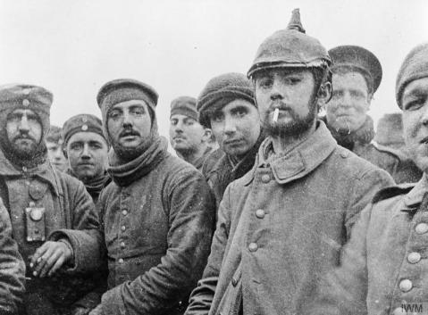 Image © IWM (Q 11745) – British and German soldiers fraternising at Ploegsteert, Belgium, on Christmas Day 1914. Possibly Riflemen Andrew (middle) and Grigg (second from the right, background) of the London Rifle Brigade with troops of the 104th and 106th Saxon Regiments.