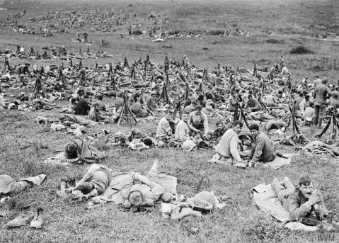 Image © IWM (Q 723) – Troops of the Royal Welsh Fusiliers at rest after being relieved from the trenches; near Acheux, 28th June 1916.