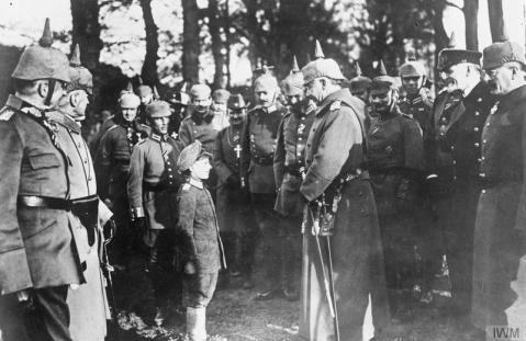 Image © IWM (Q 52767) – Kaiser Wilhelm II is amused at an orphan adopted by the troops during an inspection of troops with Prince Heinrich of Prussia. Note uniform of the Chaplain in the centre background of the group.