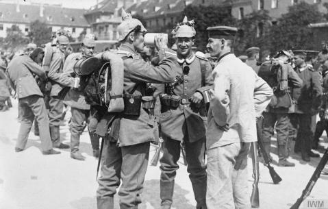 Image © IWM (Q 50349) – Bavarian troops, with their pickelhaube helmets decorated with flowers, preparing to move off for a forward area. One of the soldiers quickly finishing his pint of beer. Photograph probably taken in 1914.