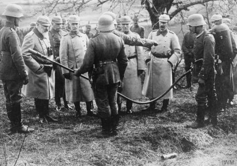 Image © IWM (Q 52257) – King Wilhelm II of Wurttemberg examining a flamethrower on the Western Front, April 1917.