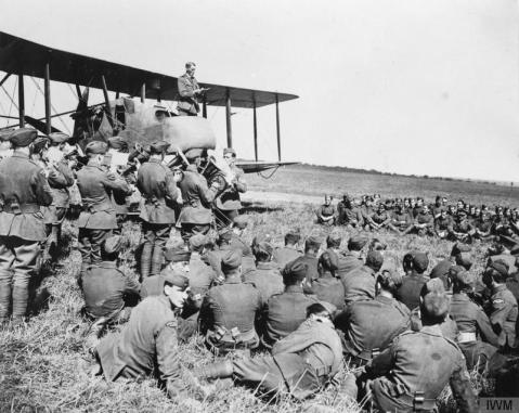 Image © IWM (Q 12109) – A chaplain conducting church service from the nacelle of a Royal Aircraft Factory F.E.2b night bomber at No. 2 Aeroplane Supply Depot, 1 September 1918. Note a military band on left in RFC uniforms playing.