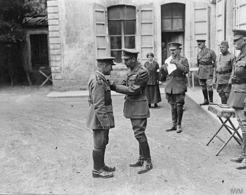 Image © IWM (Q 11128) –  King George V presents the VC to the Reverend T B Hardy, Army Chaplain, at Third Army HQ at Frohen-le-Grand, 9 August 1918.