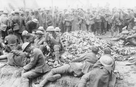 Image © IWM (Q 23670) – British prisoners of war with a heap of discarded gas masks at a German temporary POW camp on the Western Front.